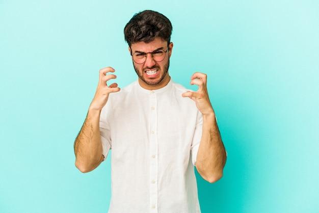 Jonge blanke man geïsoleerd op blauwe achtergrond boos schreeuwen met gespannen handen.