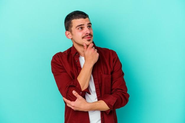 Jonge blanke man geïsoleerd op blauwe achtergrond denken en opzoeken, reflecterend zijn, nadenken, een fantasie hebben.