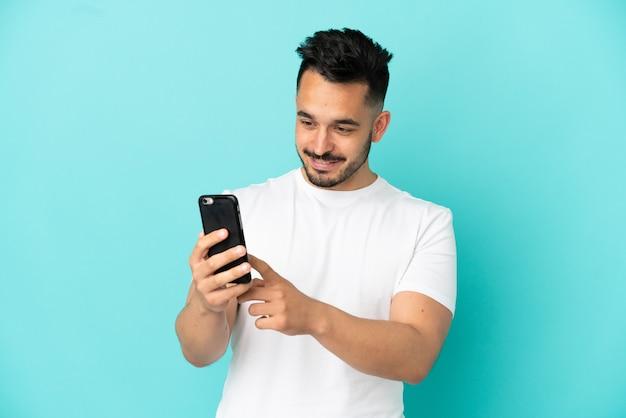Jonge blanke man geïsoleerd op blauwe achtergrond die een bericht of e-mail verzendt met de mobiel