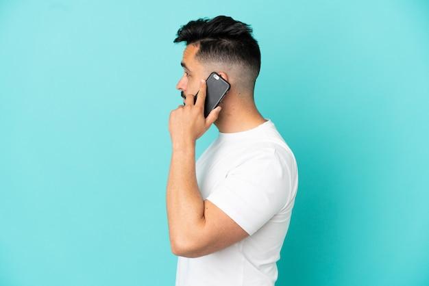 Jonge blanke man geïsoleerd op blauwe achtergrond die een gesprek voert met de mobiele telefoon met iemand