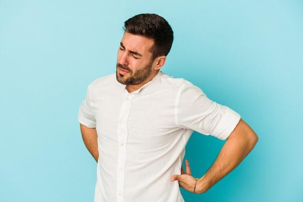 Jonge blanke man geïsoleerd op blauwe achtergrond die lijdt aan rugpijn.