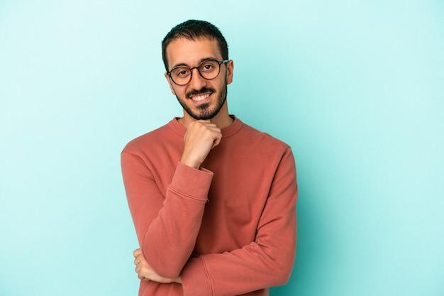 Jonge blanke man geïsoleerd op blauwe achtergrond glimlachend gelukkig en zelfverzekerd, kin met de hand aan te raken.