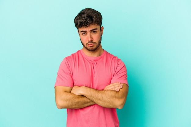 Jonge blanke man geïsoleerd op blauwe achtergrond haalt zijn schouders op en verwarde ogen.