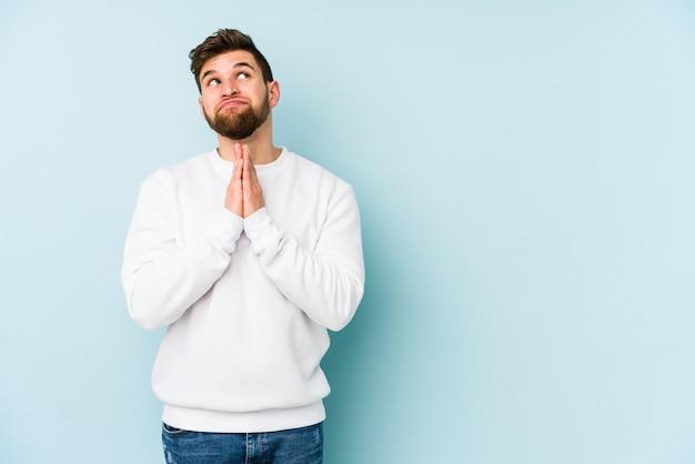 Jonge blanke man geïsoleerd op blauwe achtergrond hand in hand bidden in de buurt van de mond, voelt zich zelfverzekerd.