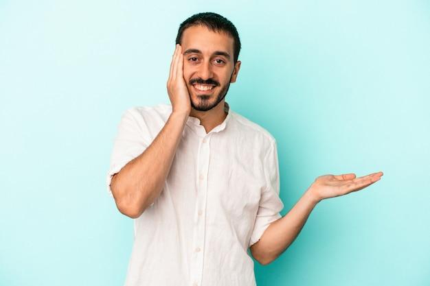 Jonge blanke man geïsoleerd op blauwe achtergrond houdt kopieerruimte op een handpalm, hand over wang. verbaasd en verheugd.