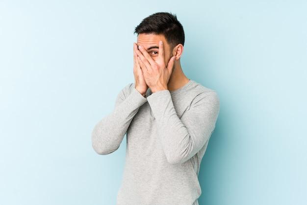 Jonge blanke man geïsoleerd op blauwe achtergrond knipperen door vingers bang en nerveus.