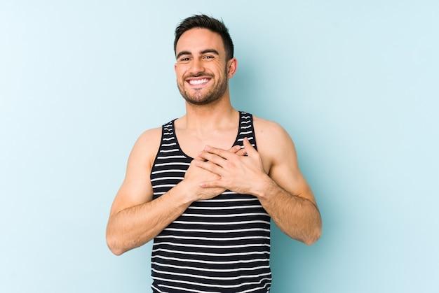Jonge blanke man geïsoleerd op blauwe achtergrond lachen houden handen op hart, concept van geluk.