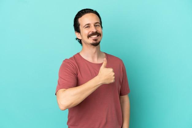 Jonge blanke man geïsoleerd op blauwe achtergrond met een duim omhoog gebaar