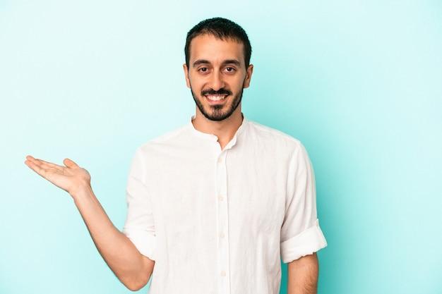 Jonge blanke man geïsoleerd op blauwe achtergrond met een kopie ruimte op een palm en met een andere hand op de taille.