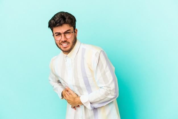 Jonge blanke man geïsoleerd op blauwe achtergrond met een leverpijn, buikpijn.