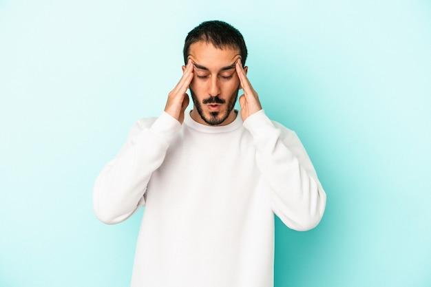 Jonge blanke man geïsoleerd op blauwe achtergrond met hoofdpijn, aanraken van de voorkant van het gezicht.