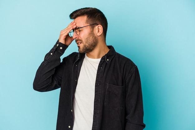 Jonge blanke man geïsoleerd op blauwe achtergrond met hoofdpijn, voorkant van het gezicht aan te raken.