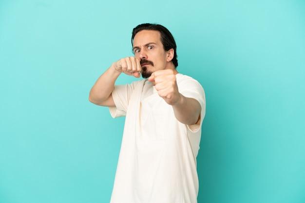 Jonge blanke man geïsoleerd op blauwe achtergrond met vechten gebaar