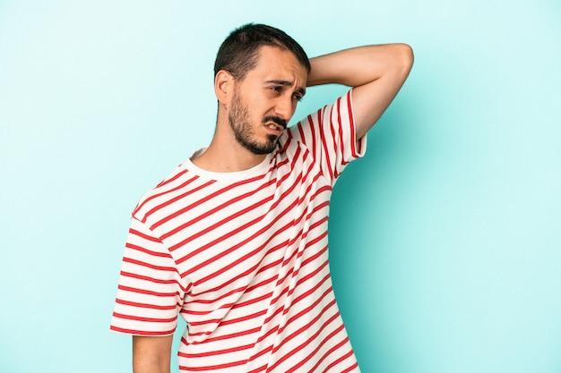 Jonge blanke man geïsoleerd op blauwe achtergrond moe en erg slaperig hand op het hoofd houden.