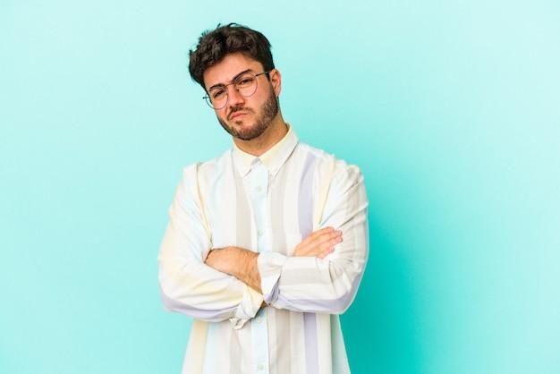 Jonge blanke man geïsoleerd op blauwe achtergrond ongelukkig in de camera kijken met sarcastische uitdrukking.
