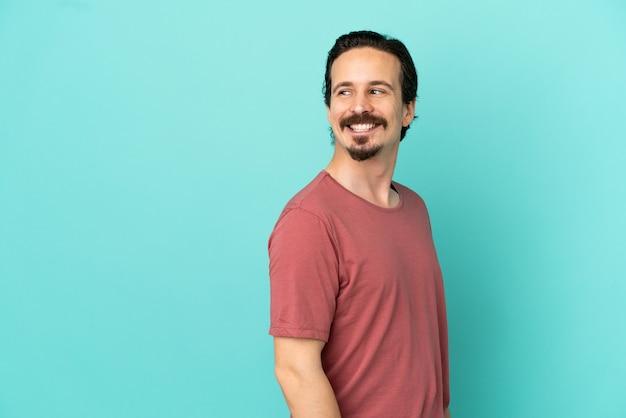 Jonge blanke man geïsoleerd op blauwe achtergrond op zoek naar de kant en glimlachend
