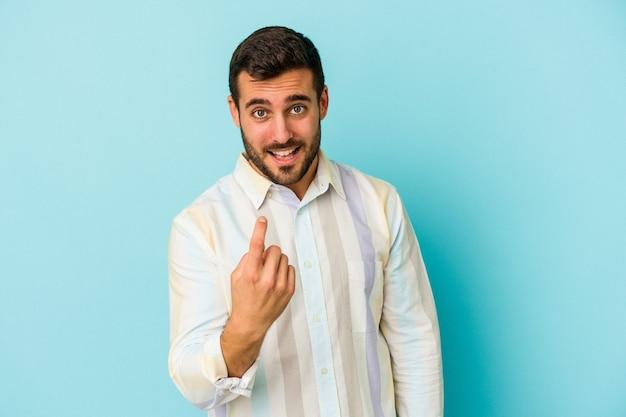 Jonge blanke man geïsoleerd op blauwe achtergrond wijzend met de vinger naar je alsof uitnodigend dichterbij komen.