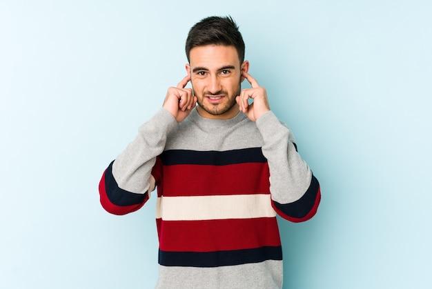 Jonge blanke man geïsoleerd op blauwe kegelvormige oren met vingers, gestrest en wanhopig door een luid ambient.