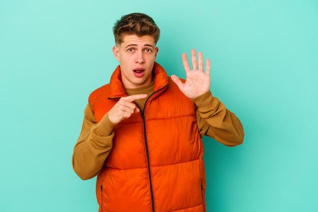 Jonge blanke man geïsoleerd op blauwe muur glimlachend vrolijk tonend nummer vijf met vingers