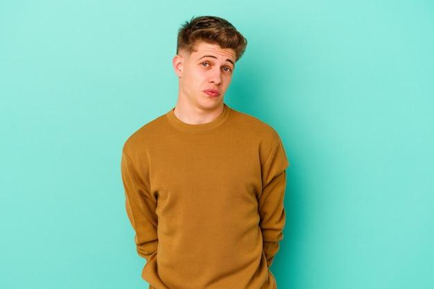 Jonge blanke man geïsoleerd op blauwe muur haalt schouders en open ogen verward op