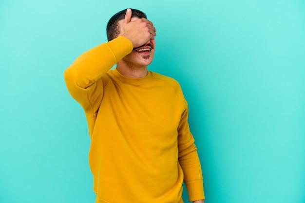 Jonge blanke man geïsoleerd op blauwe muur lacht vreugdevol handen op het hoofd te houden. geluk concept.