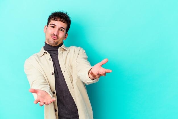 Jonge blanke man geïsoleerd op blauwe muur lippen vouwen en palmen vasthouden om luchtkus te sturen. Premium Foto