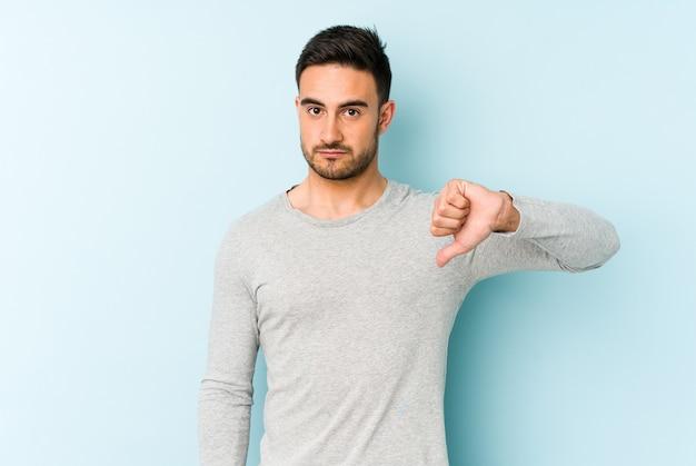Jonge blanke man geïsoleerd op blauwe muur met een afkeer gebaar, duimen naar beneden. meningsverschil concept.