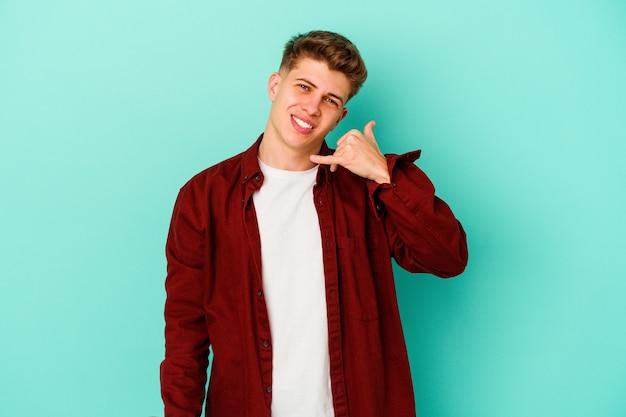 Jonge blanke man geïsoleerd op blauwe muur met een gebaar van de mobiele telefoongesprek met vingers