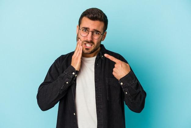 Jonge blanke man geïsoleerd op blauwe muur met een sterke tandenpijn, kiespijn.
