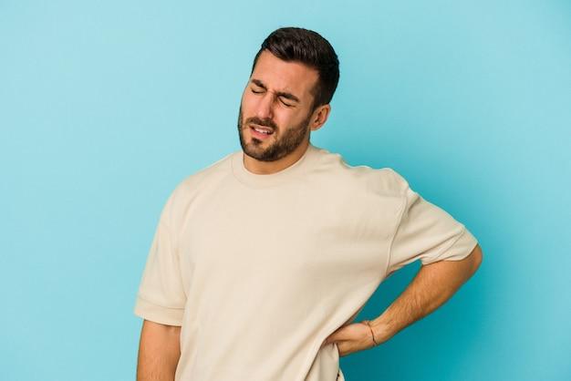 Jonge blanke man geïsoleerd op blauwe muur met rugpijn.