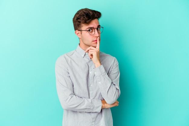 Jonge blanke man geïsoleerd op blauwe muur ongelukkig in de camera kijken met sarcastische uitdrukking