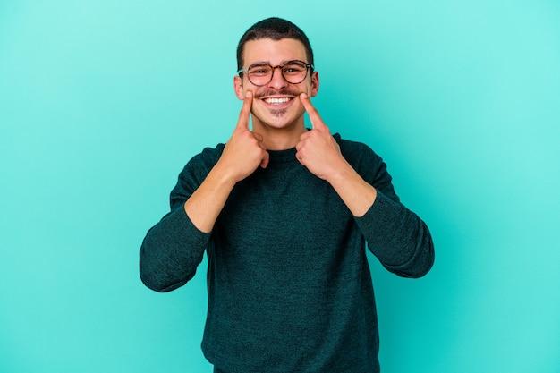 Jonge blanke man geïsoleerd op blauwe muur twijfelen tussen twee opties