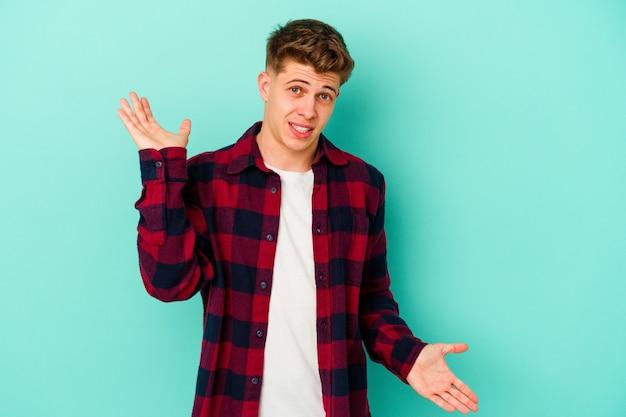 Jonge blanke man geïsoleerd op blauwe muur verward en twijfelachtig schouders ophalen om een kopie ruimte vast te houden