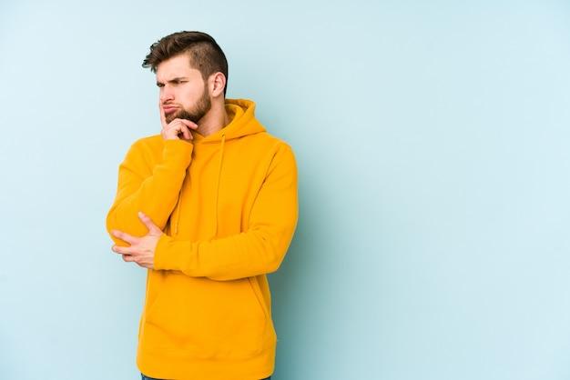 Jonge blanke man geïsoleerd op blauwe ruimte overweegt, een strategie plannen, nadenken over de manier van een bedrijf.