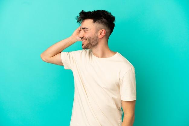 Jonge blanke man geïsoleerd op een blauwe achtergrond die een gesprek voert met de mobiele telefoon met iemand