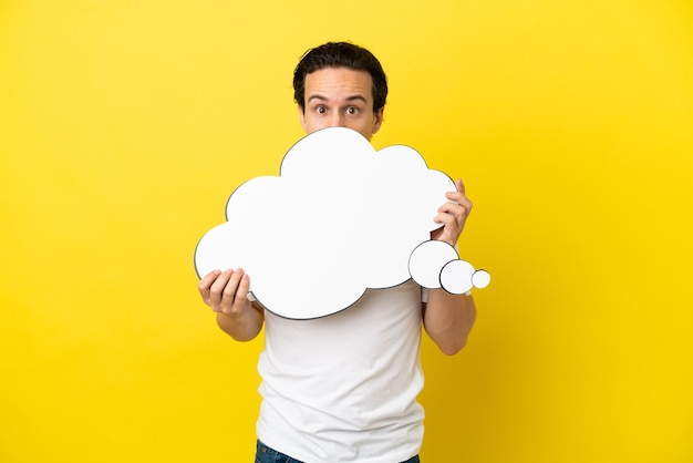 Jonge blanke man geïsoleerd op een gele achtergrond die een denkende tekstballon vasthoudt en erachter verstopt