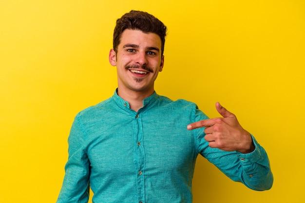 Jonge blanke man geïsoleerd op een gele achtergrond persoon die met de hand wijst naar een shirt kopieerruimte, trots en zelfverzekerd and