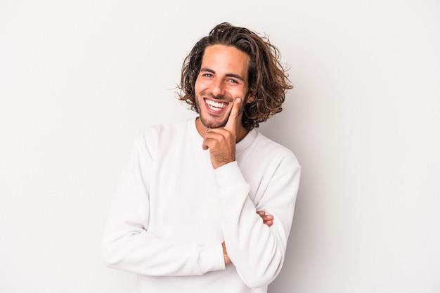 Jonge blanke man geïsoleerd op een grijze achtergrond glimlachend gelukkig en zelfverzekerd, kin met de hand aan te raken.