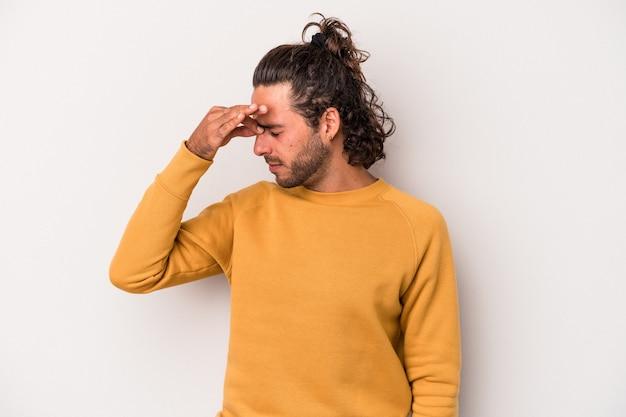 Jonge blanke man geïsoleerd op een grijze achtergrond met hoofdpijn, aanraken van de voorkant van het gezicht.