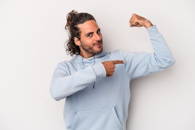 Jonge blanke man geïsoleerd op een grijze achtergrond met krachtgebaar met armen, symbool van vrouwelijke kracht