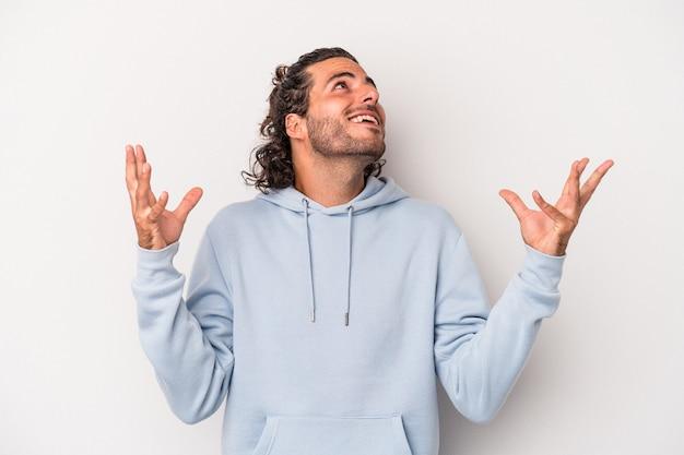Jonge blanke man geïsoleerd op een grijze achtergrond schreeuwen naar de hemel, opzoeken, gefrustreerd.