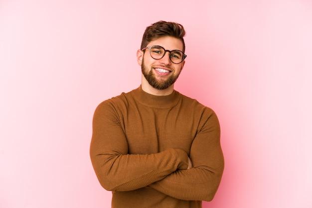 Jonge blanke man geïsoleerd op een roze muur die zich zelfverzekerd voelt en vastberaden de armen kruist.