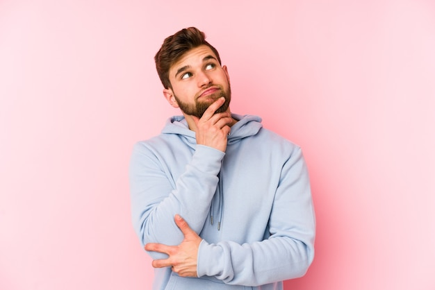 Jonge blanke man geïsoleerd op een roze muur opzij kijkt met twijfelachtige en sceptische uitdrukking.