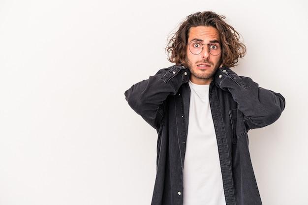 Jonge blanke man geïsoleerd op een witte achtergrond achterhoofd aanraken, denken en een keuze maken.