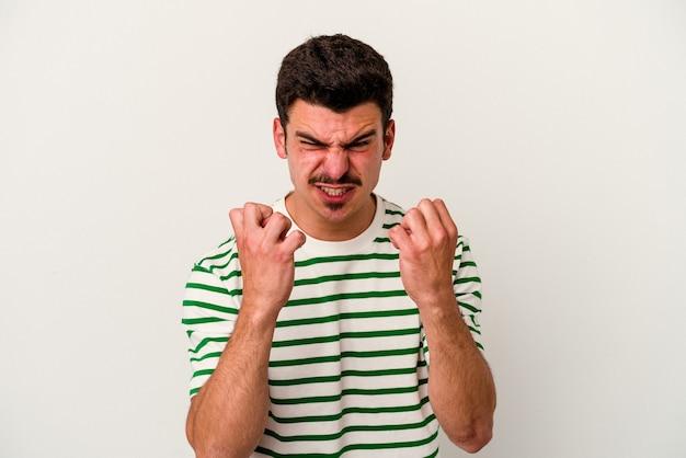 Jonge blanke man geïsoleerd op een witte achtergrond boos schreeuwen met gespannen handen.