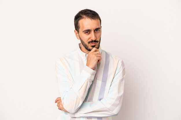 Jonge blanke man geïsoleerd op een witte achtergrond denken en opzoeken, reflecterend zijn, nadenken, een fantasie hebben.