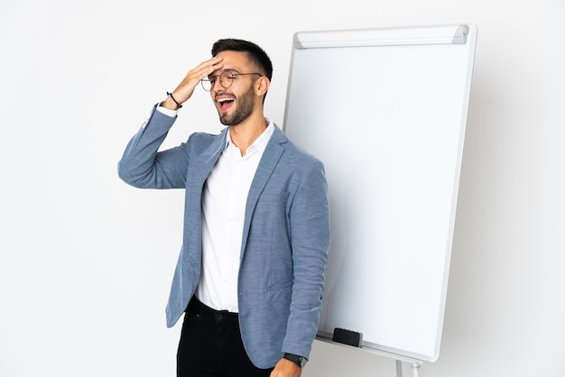 Jonge blanke man geïsoleerd op een witte achtergrond die een presentatie geeft op een wit bord en terwijl hij de oplossing voor ogen heeft