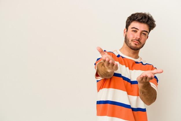 Jonge blanke man geïsoleerd op een witte achtergrond die lippen vouwt en handpalmen vasthoudt om luchtkus te sturen.
