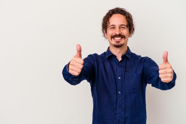 Jonge blanke man geïsoleerd op een witte achtergrond glimlachend en duim opheffen