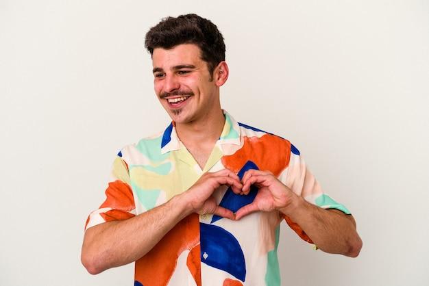 Jonge blanke man geïsoleerd op een witte achtergrond glimlachend en toont een hartvorm met handen.